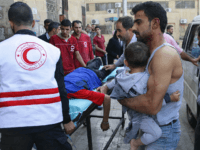 A Syrian man carries a child as they await treatment at a hospital in the regime-held part of Aleppo on October 13, 2016. Syrian state television said four children were killed by rebel rocket fire on a school in a western regime-held neighbourhood. / AFP / GEORGE OURFALIAN (Photo credit …