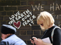 People walk past anti-fracking messages written on a wall during a demonstration outside Lancashire County Hall in Preston, northwest England, on June 23, 2015 against the applications from energy firm Cuadrilla to start two fracking operations on nearby sites. Lancashire County Council were expected to vote on June 24 on …
