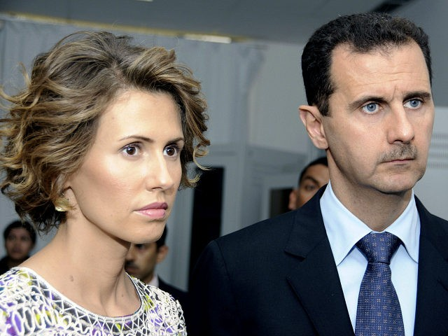 FILE - In this Tuesday, July 13, 2010 file photo, Syrian President Bashar Assad, right, and his wife Asma Assad, listen to explanations as they visit a technology plant in Tunis. In the eyes of many, Assad is a murderous autocrat who would do anything to cling to power. But for his supporters, he is a nationalist hero fighting Western imperialism, a stabilizing presence who ensures a secular rule in a turbulent region wracked by sectarian wars. (AP Photo/Hassene Dridi, File)