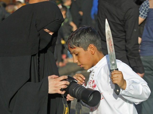 An Iraqi Shiite boy looks at his picture during the reenactment of the Battle of Karbala, as part of a parade in preparation for the peak of the mourning period of Ashura, on October 11, 2016 in Baghdad's northern district of Kadhimiya. The religious festival of Ashura, which includes a …