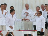 Colombia's President Juan Manuel Santos, front left, gives a peace pin to the top commander of the Revolutionary Armed Forces of Colombia, FARC, Rodrigo Londono, known by the alias Timochenko after they signed a peace agreement between the government and the FARC in Cartagena, Colombia, Monday, Sept. 26, 2016. Colombians …