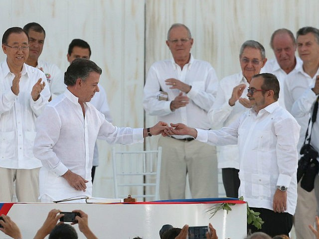 Colombia's President Juan Manuel Santos, front left, gives a peace pin to the top commander of the Revolutionary Armed Forces of Colombia, FARC, Rodrigo Londono, known by the alias Timochenko after they signed a peace agreement between the government and the FARC in Cartagena, Colombia, Monday, Sept. 26, 2016. Colombians are being given the final say on endorsing or rejecting the accord in an Oct. 2 referendum. (AP Photo/Fernando Vergara)