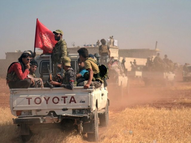 Syrian rebel fighters ride in the back of a pick-up truck flying an Islamist flag in the northern Syrian village of Rael after they captured it from the Islamic State (IS) group in the Marj Dabiq area north of the embattled city of Aleppo on October 9, 2016. / AFP …