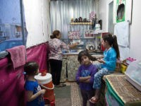Intisar Mateh, second left, washes the dishes as her daughter, Farah Mateh, right, plays with her friends in a camp for displaced Christians in Irbil, Iraq, Friday, Oct. 21, 2016. Iraqi refugees from areas near Mosul are eagerly following the offensive to drive the Islamic State group from the city and hope to return to their homes, but they also fear what they might find there. (AP Photo/Fay Abuelgasim)