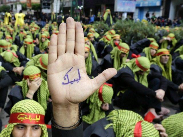A supporter of Lebanon's militant Shiite Muslim movement Hezbollah shows his hand reading in Arabic 'answering your call [Hussein]' during a parade as part of the Ashura commemorations that mark the killing of Imam Hussein -one of Shiite Islam's most revered figures- on November 4, 2014 in the capital Beirut's southern suburbs. The commemoration comes a day after Hezbollah chief Hassan Nasrallah made a rare appearance in the southern suburbs, calling on supporters to take part in Ashura despite 'any threat, any danger, any challenge'. AFP PHOTO / ANWAR AMRO (Photo credit should read ANWAR AMRO/AFP/Getty Images)