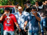 A police official, center, escorts two men outside the court in Thane, outskirts of Mumbai, India, Thursday, Oct. 6, 2016. Indian police have arrested 70 people and are questioning hundreds more after uncovering a massive scam to cheat thousands of Americans out of millions of dollars by posing as U.S. tax authorities and demanding unpaid taxes. (AP Photo/Rajanish Kakade)