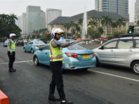 Police officers stand on a main road in Jakarta on Aug. 30, 2016, as a new traffic control system is introduced in the capital. Under the system, vehicles with odd-numbered plates are allowed to run on main roads during peak morning and evening hours on odd-numbered dates and those with even-numbered plates can run on the main roads on even-numbered dates. (Kyodo via AP Images) ==Kyodo