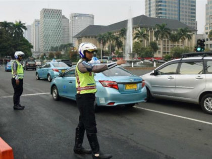 Police officers stand on a main road in Jakarta on Aug. 30, 2016, as a new traffic control system is introduced in the capital. Under the system, vehicles with odd-numbered plates are allowed to run on main roads during peak morning and evening hours on odd-numbered dates and those with …