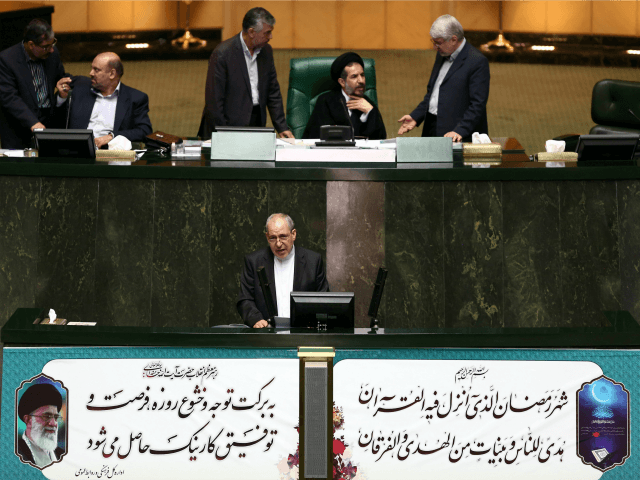Iranian education minister Ali Asghar Fani (bottom) defends himself during a parliament session to impeach him in Tehran on June 24, 2015. The Iranian educaton minister safely came out of an impeachment session, as the conservative majority threw their weight behind him in an unlikely show of support. AFP PHOTO …