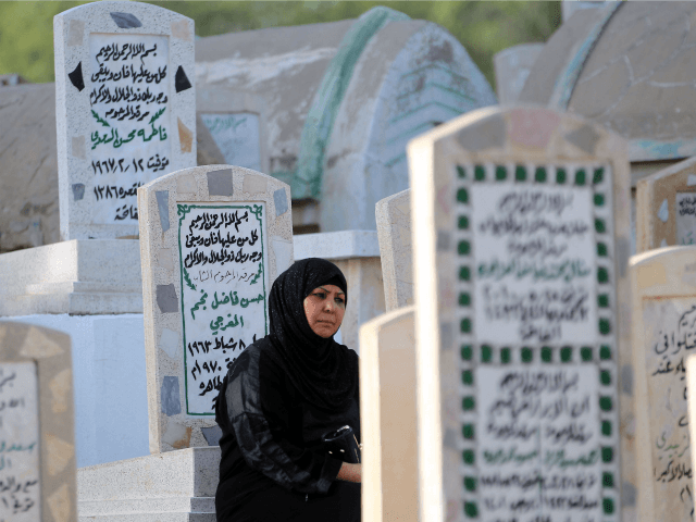 An Iraqi woman prays at the grave of a loved one at a cemetery in the capital Baghdad on July 6, 2016 on the first day of Eid al-Fitr holiday, which marks the end of the holy Muslim fasting month of Ramadan. / AFP / AHMAD AL-RUBAYE (Photo credit should …