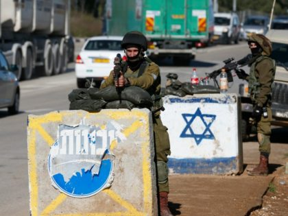 Israeli soldiers keep watch at the Gush Etzion junction, south of Jerusalem in the Israeli-occupied West Bank, following a car ramming attack on March 4, 2016. A Palestinian woman injured an Israeli soldier in the car-ramming attack before troops at the scene shot her dead, the army said. / AFP …
