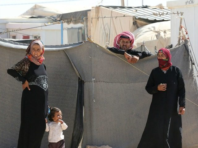 Syrian refugees stand at the Zaatari refugee camp, located close to the northern Jordanian city of Mafraq near the border with Syria, on July 14, 2016. Zaatari camp, 80 kilometres (50 miles) north of the capital Amman, is home to some 80,000 refugees from the brutal war in neighbouring Syria. …