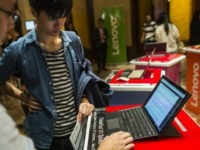 Attendees look at a Lenovo Group Ltd. ThinkPad X1 laptop computer ahead of a news conference in Hong Kong, China, on Thursday, May 26, 2016. Lenovo posted fourth-quarter profit that missed analysts' estimates as it struggles to revive the Motorola smartphone brand and the personal computer market continues to slide. …