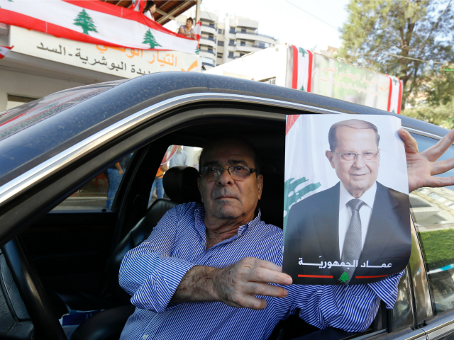 A supporter of Lebanese presidential candidate Michel Aoun holds his portrait ahead of a parliament session expected to elect the ex-general as president and end a political stalemate of more than two years, as they gather in Jdeidah, on the northern outskirts of the capital Beirut on October 31, 2016. …