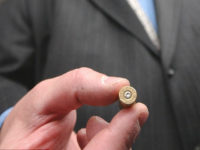Todd Lizotte holds a cartridge case fired from a handgun marked with microstamping technology he developed, Friday, May 18, 2007, on Capitol Hill in Washington. (AP Photo/Dennis Cook)