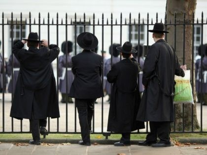 LONDON, ENGLAND - NOVEMBER 05: Orthodox Jews watch the Grenadier Guards participating in ceremonial duties at Wellington Barracks on November 5, 2009 in London, England. Three Grenadier Gurardsmen were amongst the five soldiers who were shot dead during an attack by a rogue member of the Afghan police force. Two …