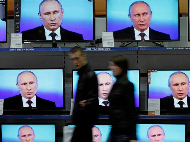 Visitors walk past TV sets during Russian President Vladimir Putin's live broadcast nationwide phone-in at the DNS electronic shop in Russia's Siberian city of Krasnoyarsk. Credit: Ilya Naymushin/Reuters