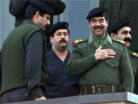 BAGHDAD, IRAQ: Iraqi President Saddam Hussein (2nd R), surrounded by body guards, salutes the crowd during a military parade in Baghdad late 20 November 2000. Thousands of Iraqis marched through the center of the Iraqi capital to demonstrate their readiness to take part in a jihad or holy war against Israel as Baghdad claims to have recruited 6.6 million volunteers to fight against Israel alongside the Palestinian uprising. AFP PHOTO/Karim SAHIB (Photo credit should read KARIM SAHIB/AFP/Getty Images)