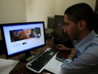 A Palestinian man looks at the Facebook page of Avichay Adraee, the spokesman of the Israeli Army to the Arabic media, after hackers replaced his cover photo with that of the Ezzedine al-Qassam Brigade during the '#Op_Israel' campaign launched by the activist group Anonymous, in Gaza City on April 7, …