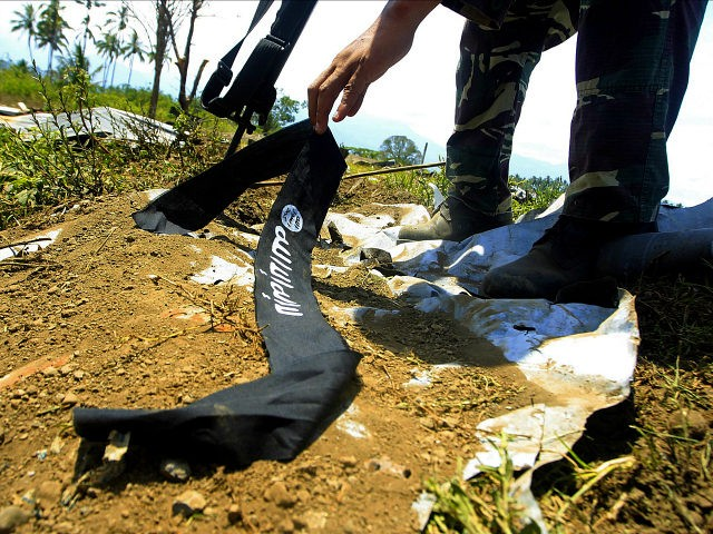 A Philippine soldier picks up the headband of a militant, adorned with the logo used by the Islamic State group, as they end their operation in Butig Town, Lanao Del Sur on the southern Philippine island of Mindanao on March 1, 2016. At least six people have been killed and more than 20,000 displaced during a week of fighting between Islamic militants and security forces in the southern Philippines, authorities said February 26. Three soldiers and three militants were confirmed killed in the clashes, which involved followers of a slain Indonesian leader of a Southeast Asian militant group, the military said. AFP PHOTO / MARK NAVALES / AFP / MARK NAVALES (Photo credit should read MARK NAVALES/AFP/Getty Images)