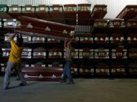 Workers carry a coffin in a caskets factory in Caracas November 29, 2012. REUTERS/Carlos Garcia Rawlins