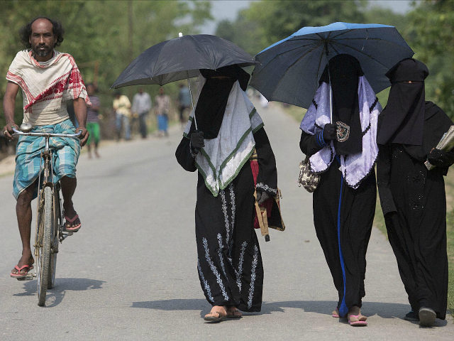 An Indian villager pedals past Burqa clad Muslim students walking to a school at Burhaburhi village about 60 kilometers (38 miles) east of Gauhati, India, Thursday, April 9, 2015. (AP Photo/ Anupam Nath)