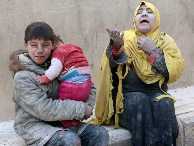A woman, a young boy and a baby, covered with dust, sit in a state of shock following a reported air strike attack by government forces on the Hanano district of the northern Syrian city of Aleppo on February 14, 2014. Syria's warring sides began what was expected to be …