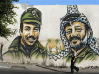 A Palestinian man walks past a graffiti of late Palestinian leader Yasser Arafat (R) and assassinated Palestine Liberation Organisation (PLO) deputy leader Khalil al-Wazir, also known as Abu Jihad, in Gaza City on August 6, 2009. Israel has for the first time admitted assassinating the PLO's former number two, Abu …