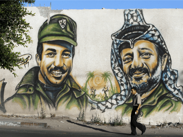 A Palestinian man walks past a graffiti of late Palestinian leader Yasser Arafat (R) and assassinated Palestine Liberation Organisation (PLO) deputy leader Khalil al-Wazir, also known as Abu Jihad, in Gaza City on August 6, 2009. Israel has for the first time admitted assassinating the PLO's former number two, Abu Jihad, in a raid on the movement's Tunis headquarters in 1988, a newspaper reported on November 1, 2012. The report, published in Israel's top-selling Yediot Aharonot, said the operation was planned by the Mossad spy agency and carried out by the Sayeret Matkal elite commando unit. AFP PHOTO/MOHAMMED ABED (Photo credit should read MOHAMMED ABED/AFP/Getty Images)