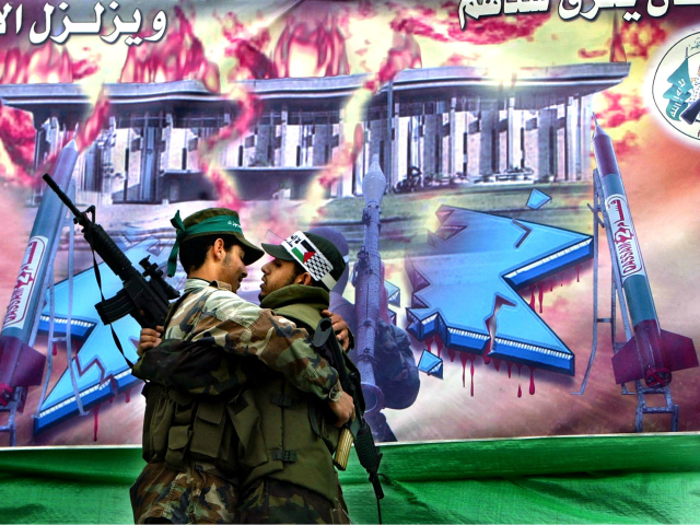 Palestinian Hamas actors dressed up as suicide bombers, one of Hamas (L) and the other of the al-Aqsa Martyrs Brigades, in a play depicting them planning the attack on the Israeli port in Ashdood in front of a painting of former Hamas spiritual leader Sheikh Ahmed Yassin, a burning Star …