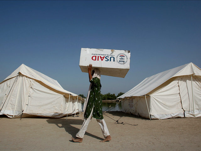 A woman, who has been displaced by floods, uses a USAID box to move her belongings while taking refuge on an embankment at Chandan Mori village in Dadu, some 320 km (199 miles) north of Karachi October 10, 2010. REUTERS/Akhtar Soomro