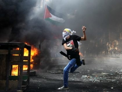 A masked Palestinian hurls rocks towards Israeli soldiers during clashes following the funeral of Mohammed Fares al-Jaabari on October 10, 2015, in the center of the West Bank town of Hebron. Israeli security forces have arrested approximately 400 Palestinians since the October 1 outbreak of violence in the occupied West …