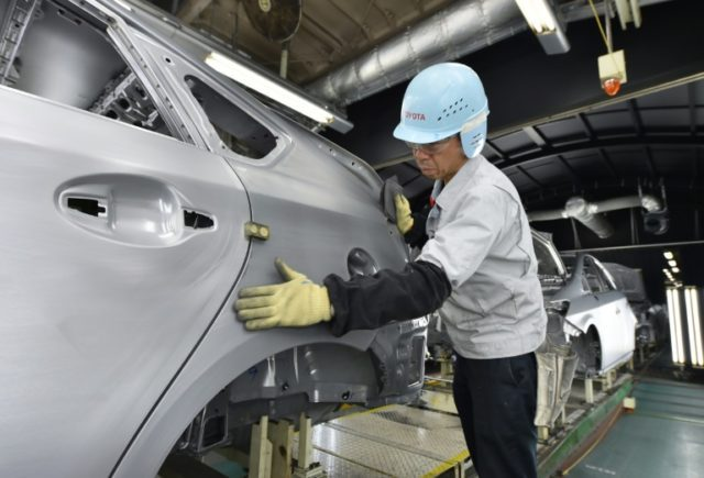 A worker makes surface inspections before the painting process on the production line at Toyota's Tsutsumi plant in Japan's Aichi prefecture