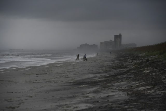 People bike on the beach ahead of hurricane Matthew in Atlantic Beach, Florida, on October 5, 2016
