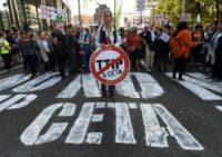 A woman holds a placard depicting a no entry sign with the TTIP and CETA logos, during a demonstration outside the European Union headquarters in Brussels, on September 20, 2016