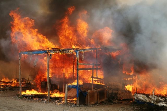 "A fire burns at the ""Jungle"" migrant camp in Calais, northern France, on October 26, 2016"