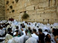 Jewish worshippers attend the annual Cohanim prayer (priest's blessing) during the Sukkot holiday, or the feast of the Tabernacles, at the Western Wall in the old city of Jerusalem on October 19, 2016. Thousands of Jews gathered at the Western Wall in Jerusalem for a holiday blessing, a day after …