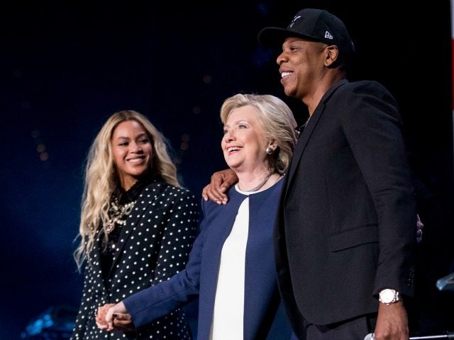 Democratic presidential candidate Hillary Clinton, center, appears on stage with artists Jay Z, right, and Beyonce, left, during a free concert at at the Wolstein Center in Cleveland, Friday, Nov. 4, 2016. (