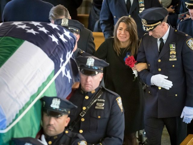 Lisa Tuozzolo, wife of the late Sgt. Paul Tuozzolo is escorted by a high ranking New York Police Department officer, at the conclusion of Tuozzolo's Mass of Christian Burial at St. Rose of Lima Catholic Church in Massapequa, N.Y., Thursday Nov. 10, 2016.The 19-year veteran officer was killed Nov. 4, …