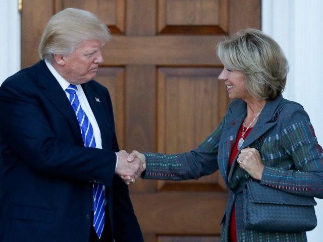 President-elect Donald Trump and Betsy DeVos shake hands at Trump National Golf Club Bedminster clubhouse in Bedminster, N.J., Saturday, Nov. 19, 2016. ()
