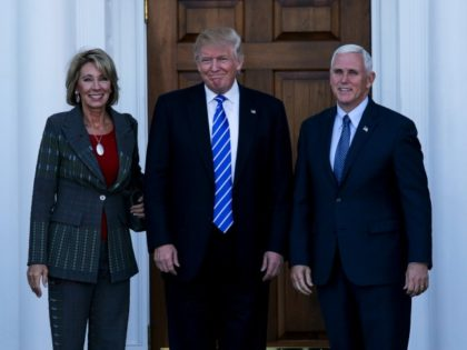 United States President-elect Donald Trump (C) and Vice President-elect Mike Pence (R) pose with Betsy DeVos at the clubhouse of Trump International Golf Club, November 19, 2016 in Bedminster Township, New Jersey.