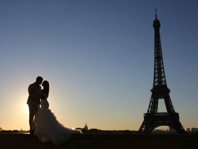 Picture taken on september 29, 2015 shows a young married couple posing for souvenirs pictures at sunrise in front of the Eiffel tower on Trocadero plaza, at sunrise, in Paris AFP PHOTO / LUDOVIC MARIN (Photo credit should read