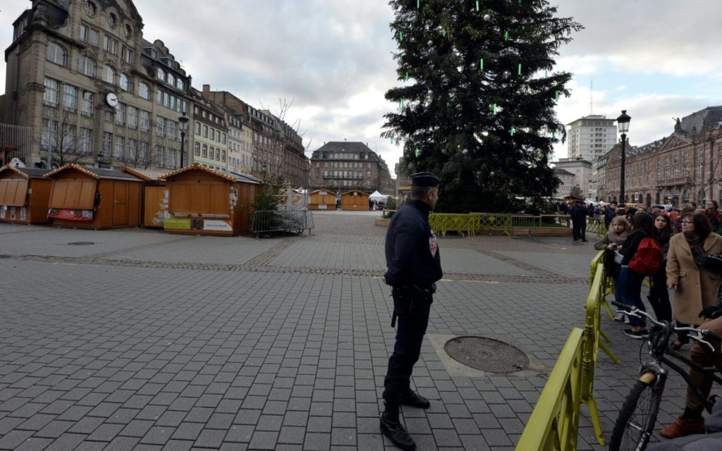 A policeman stands guard next to the central Christmas tree and closed Christmas market in Strasbourg, eastern France, on December 2, 2015. Several parcel bomb alerts occured and for security reasons the city center has been closed to road traffic during the whole period of Strasbourg's Christmas market, following the November 13 Paris terror attacks. / AFP / PATRICK HERTZOG (Photo credit should read PATRICK HERTZOG/AFP/Getty Images)