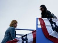 Jennifer Palmieri (L), Clinton campaign communications director, and Huma Abedin, top Clinton aid, walk past each other on the stairs to Democratic presidential nominee Hillary Clinton's campaign plane at Pueblo Memorial Airport October 12, 2016 in Pueblo, Colorado. / AFP / Brendan Smialowski (Photo credit should read