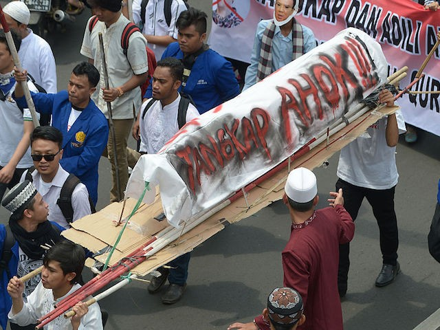 "Indonesian muslim students carry a mock coffin that reads: ""Arrest Ahok"", as Muslims march towards the presidential palace during a protest against Jakarta governor Basuki Tjahaja Purnama also known as Ahok over an alleged blasphemy in Jakarta on November 4, 2016. Tens of thousands of Muslim hardliners demanding Jakarta's governor be prosecuted for blasphemy descended on November 4 on the Indonesian capital for a massive demonstration that has authorities on their highest alert amid fears of violence. / AFP / ADEK BERRY (Photo credit should read ADEK BERRY/AFP/Getty Images)"