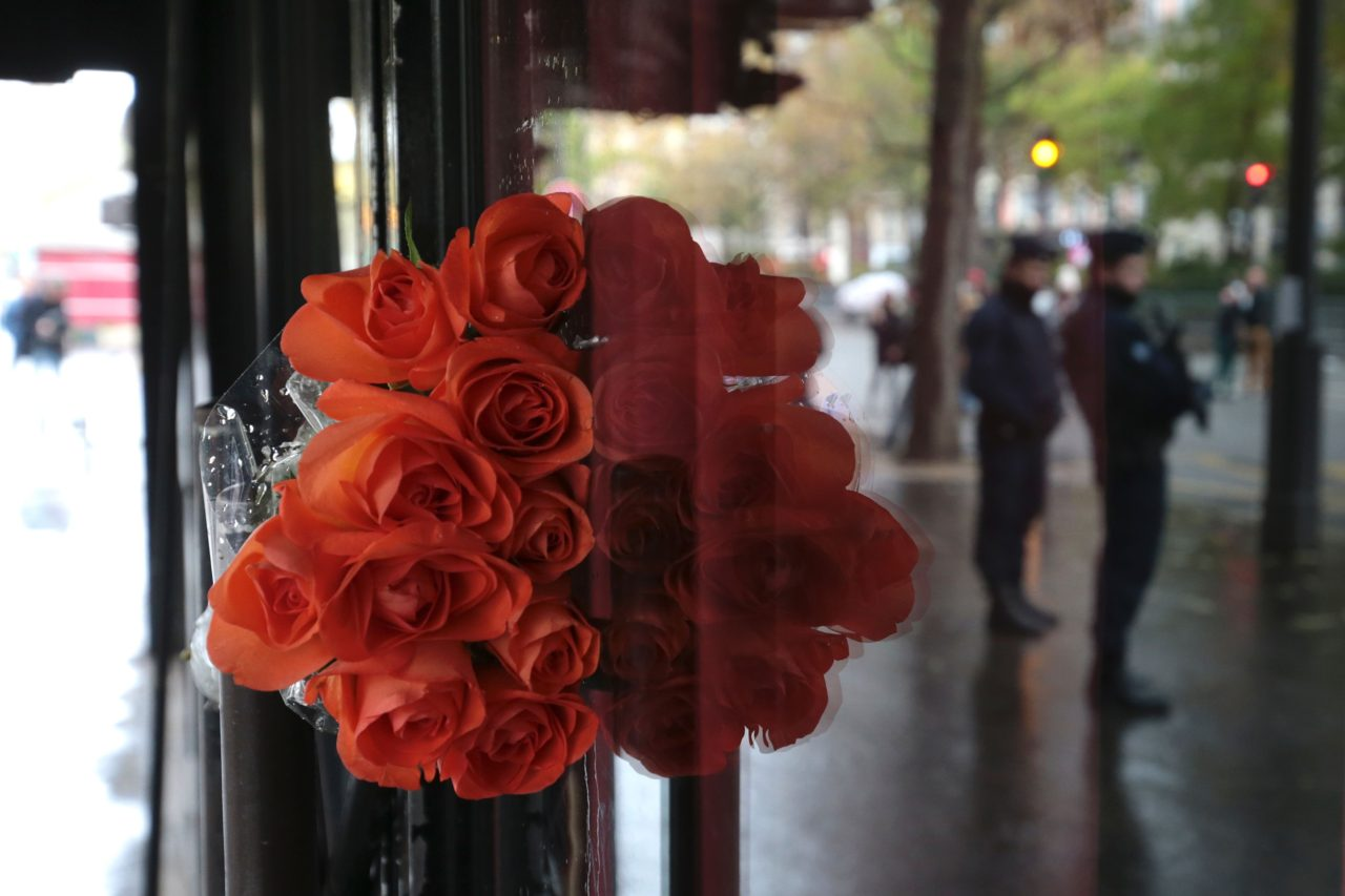 TOPSHOT - This picture taken on November 13, 2016 shows the reflection of policemen in the front door of the Bataclan Cafe in Paris where flowers were laid, after a ceremony marking the first anniversary of the Paris terror attacks. 130 people were killed on November 13, 2015 by gunmen and suicide bombers from the Islamic State (IS) group in a series of coordinated attacks in and around Paris. / AFP / JOEL SAGET (Photo credit should read JOEL SAGET/AFP/Getty Images)