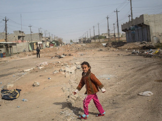MOSUL, IRAQ - NOVEMBER 15: A young girl walks across a street just behind the frontline in the Entisar neighborhood on November 15, 2016 in Mosul, Iraq. The mosul offensive has slowed due to heavy resistance from ISIL in the small streets of the outer neighbourhoods of Mosul. Residents have …