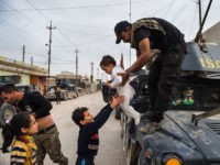 TOPSHOT - Children emerge from their houses to greet soldier from the Iraqi Special Forces 2nd division during a lull in the fighting with IS fighters while pushing into the Aden neighbourhood in Mosul on November 16, 2016. Iraqi forces have broken into jihadist-held Mosul and recaptured neighbourhoods inside the city, but a month into their offensive, there are still weeks or more of potentially heavy fighting ahead./ AFP / Odd ANDERSEN        (Photo credit should read ODD ANDERSEN/AFP/Getty Images)