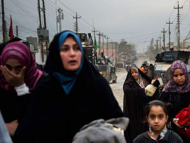 A group of women and children use the opportunity to flee during a lull in the fighting as the Iraqi Special Forces 2nd division engage IS fighters while pushing into the Aden neighbourhood in Mosul on November 16, 2016. Iraqi forces have broken into jihadist-held Mosul and recaptured neighbourhoods inside the city, but a month into their offensive, there are still weeks or more of potentially heavy fighting ahead. / AFP / Odd ANDERSEN (Photo credit should read ODD ANDERSEN/AFP/Getty Images)