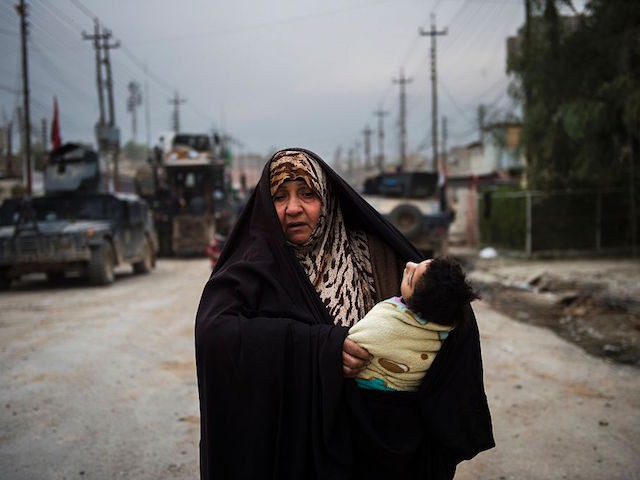 TOPSHOT - A woman carrying a handicapped child uses the opportunity to flee during a lull in the fighting as the Iraqi Special Forces 2nd division engage IS fighters while pushing into the Aden neighbourhood in Mosul on November 16, 2016. Iraqi forces have broken into jihadist-held Mosul and recaptured neighbourhoods inside the city, but a month into their offensive, there are still weeks or more of potentially heavy fighting ahead. / AFP / Odd ANDERSEN (Photo credit should read ODD ANDERSEN/AFP/Getty Images)